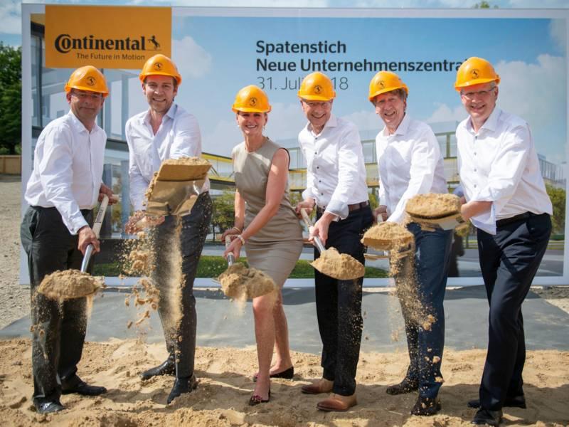Eine Frau und fünf Männer mit gelben Baustellenhelmen heben symbolisch Sand mit Spaten.