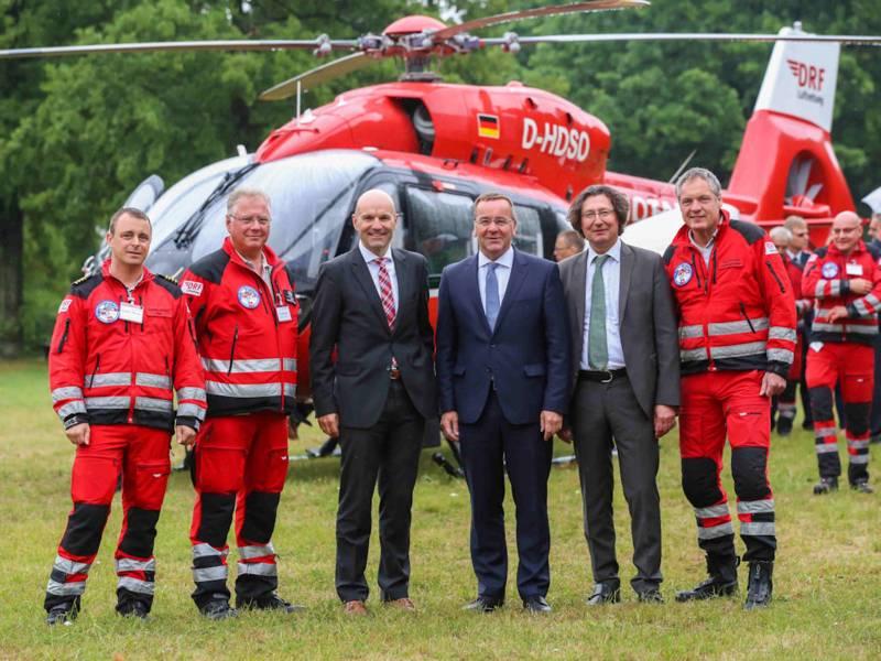 Männer posieren vor einem Hubschrauber