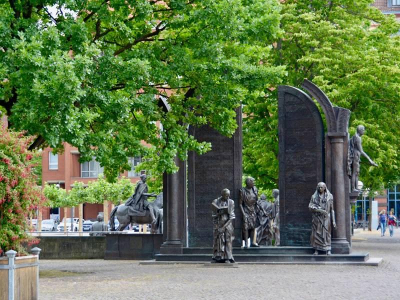 Statuen von sieben Männern zu Fuß und zu Pferd.