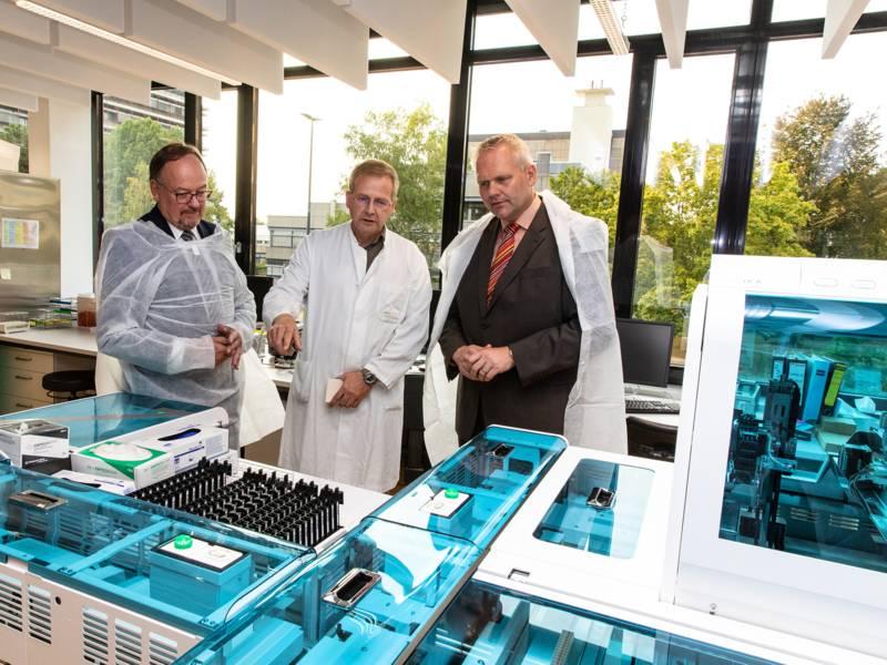 Drei Männer in einem Raum mit techischen Geräten