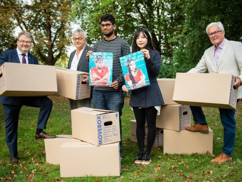 Vier Männer und eine Frau halten Plakate und Umzugskartons in den Händen