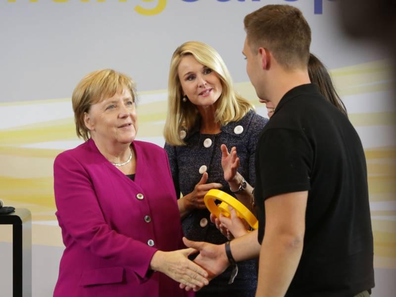 Eine Frau gibt einem Mann die Hand, zwei andere Frauen schauen zu