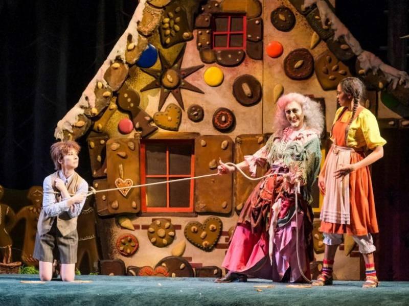 Zwei Kinder und eine Hexe vor einem großen Lebkuchenhaus.