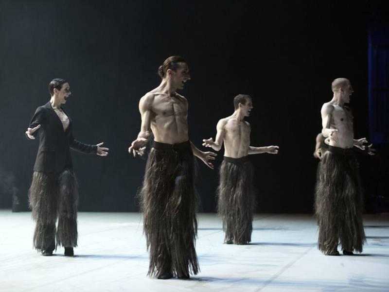 Eine Frau und drei Männer mit Hosen aus langem Fell, die Männer mit nacktem Oberkörper