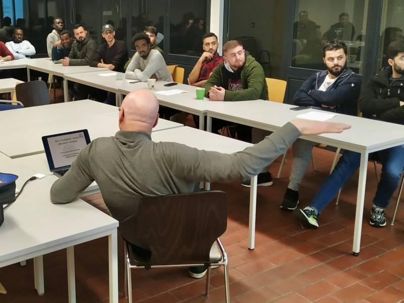 In einem Raum sitzen verschiedene Personen an Tischen, vor ihnen sitzt ein Mann, der einen Arm hebt