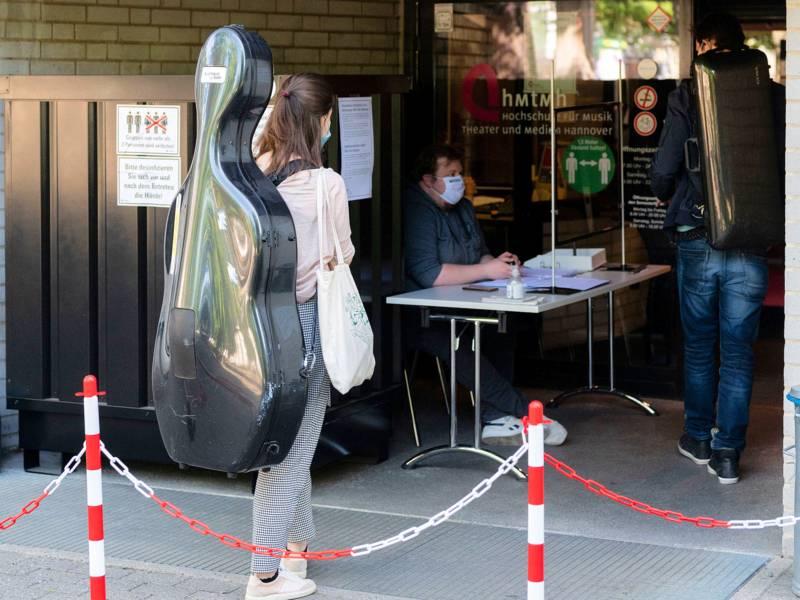 Frau mit Nasen- und Mundschutzmaske und Musikinstrumentenkoffer auf dem Rücken steht an einem kontrolliertem Eingangsbereich.
