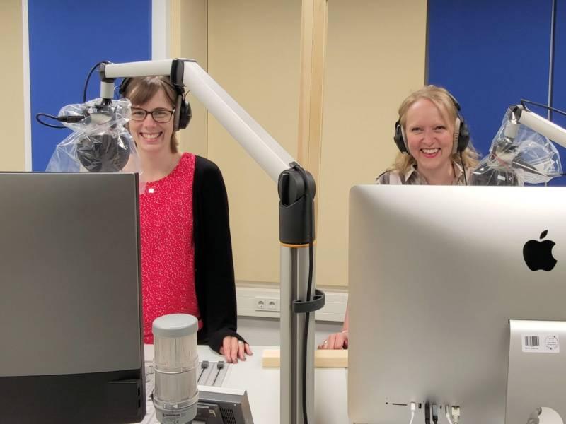 Zwei Frauen mit Kopfhörern vor Mikrophonen und Monitoren