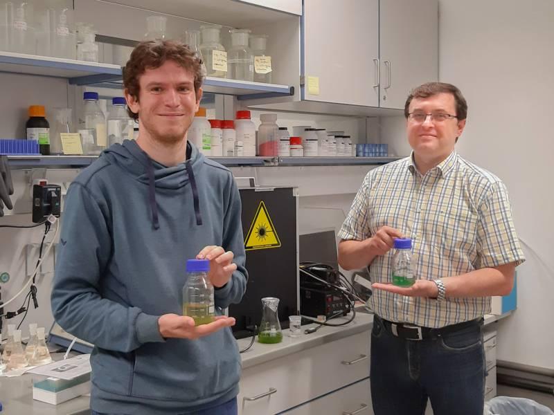 Zwei Männer in einem Labor, beide halten eine Glasflasche mit grüner Flüssigkeit in den Händen.