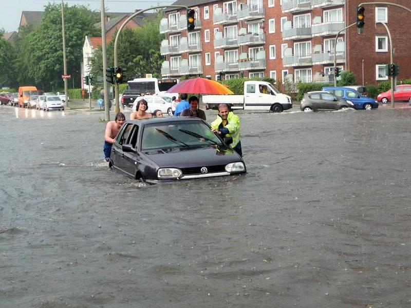 Menschen schieben ein Auto über vom Hochwasser überflutete Straße