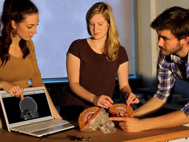 Drei junge Menschen stehen neben einem Tisch, auf dem ein Computer und das Modell eines Schädels aufgebaut sind.