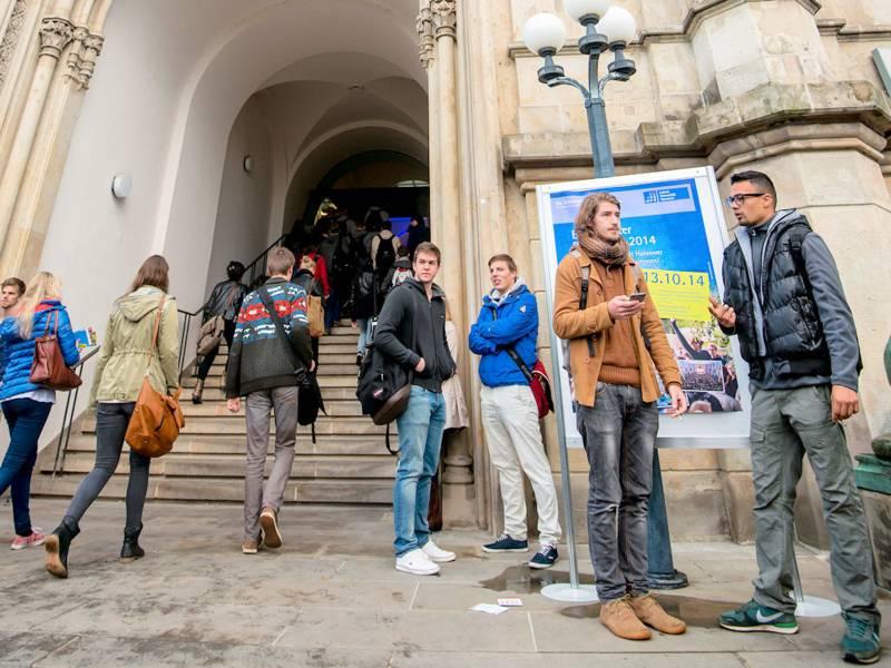 Mehrere junge Menschen vor dem Eingang eines älteren Gebäudes.