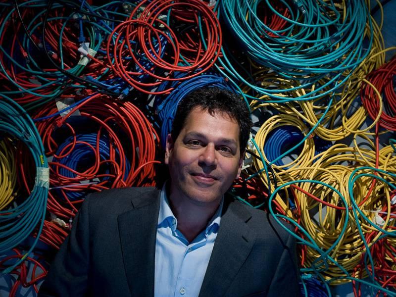 Mann vor verschiedenfarbigen aufgerollten Kabeln