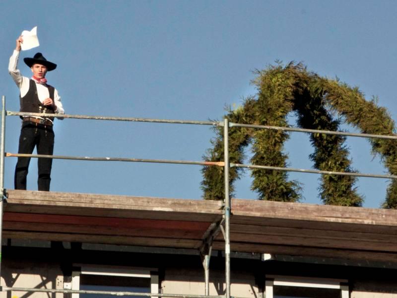 Ein Zimmermann steht neben einem Richtkranz auf einem Dach.