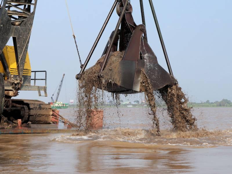 Baggerschaufel hebt Sand aus einem Gewässer