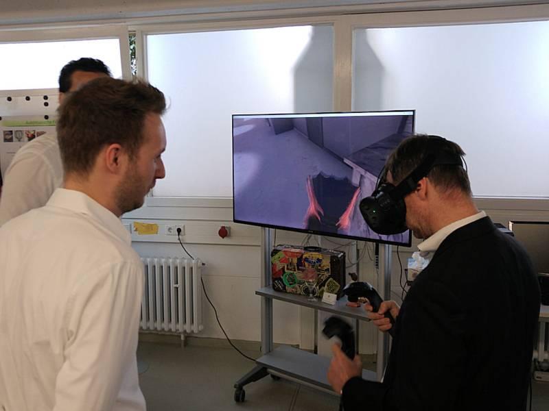 Männer vor Monitor, einer hat eine VR-Brille auf