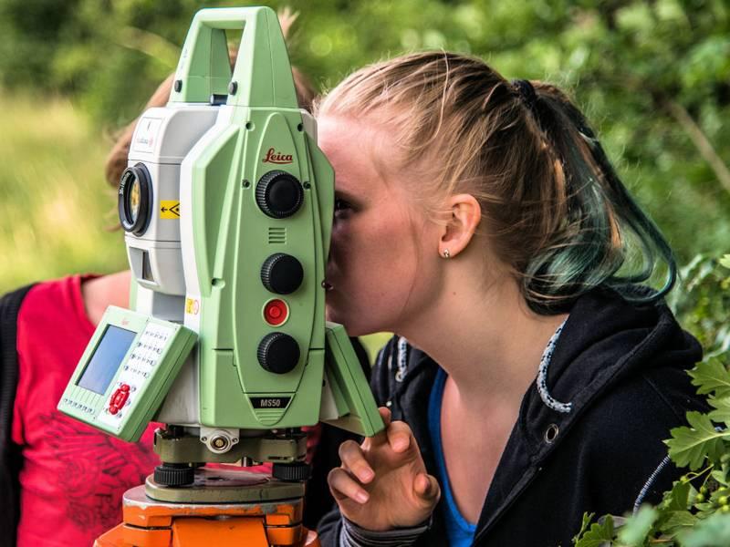 Frau blickt durch ein vermessungstechnisches Gerät