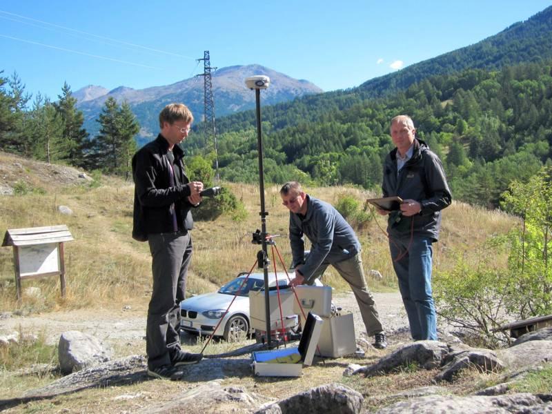 Drei Männer mit einem Messgerät im Freien.