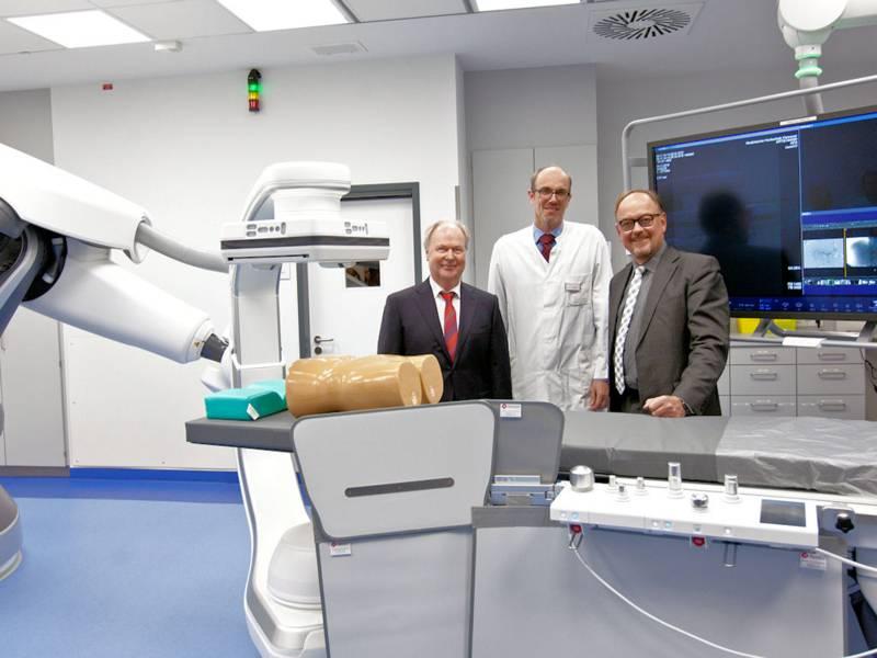 Drei Männer an medizinischem Großgerät.