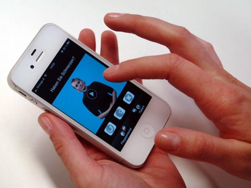 Jemand bedient ein Smartphone, auf dessen Display eine Person mit vor dem Bauch verschränkten Armen zu sehen ist, dazu der Text: Haben Sie Schmerzen?