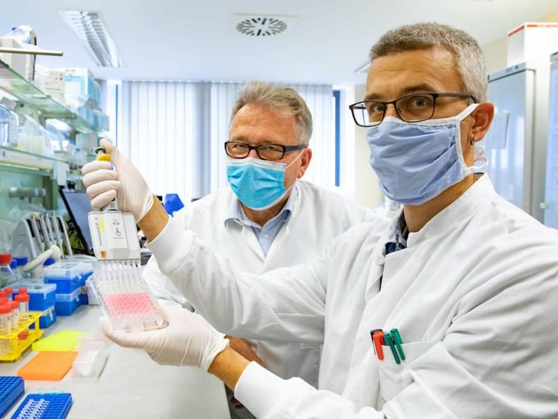 Zwei Männer mit Mund-Nasen-Schutzmasken in einem Labor.