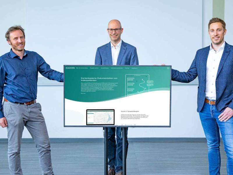 Drei Männer stehen neben und hinter einem Flachbildschirm.