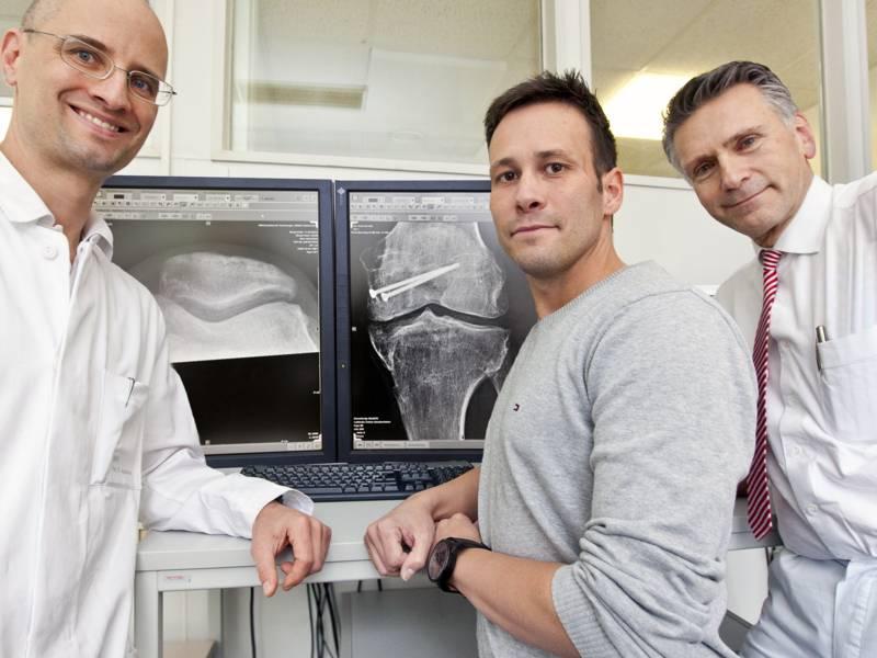 Drei Männer neben einem Bildschirm mit einer Röntgenaufnahme