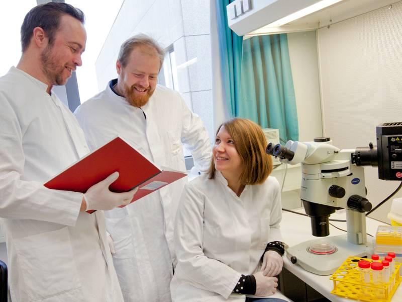 Zwei Männer stehen hinter einer Frau, die vor einem Mikroskop sitzt
