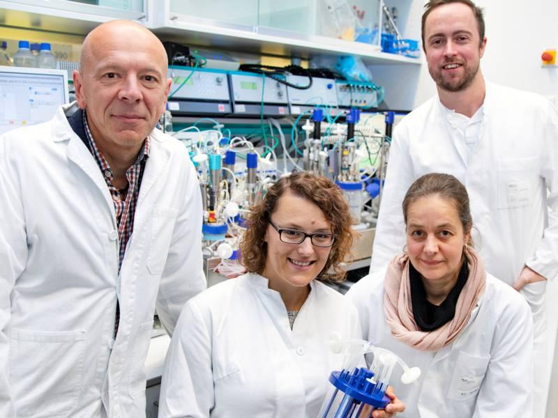 Zwei Frauen und zwei Männer in weißen Kitteln in einem Labor