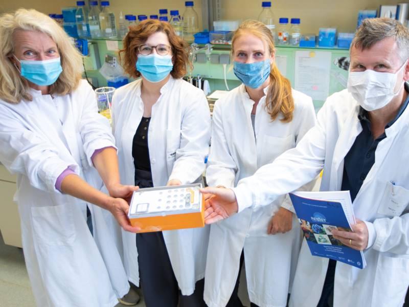 Drei Frauen und ein Mann in weißen Kitteln und mit Nasen-Mund-Schutz-Masken in einem Labor halten etwas in die Kamera.