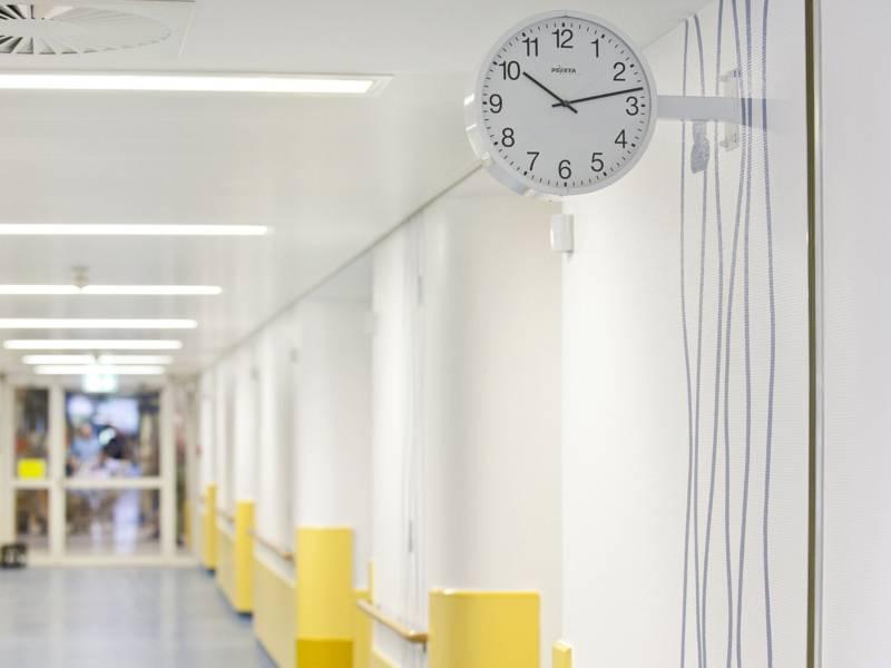 Eine Uhr hängt an der Wand in einem großen Flur.