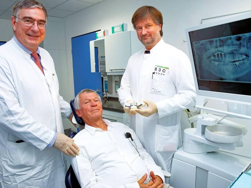 Ein Mann sitzt auf einem Behandlungsstuhl, zwei Männer stehen neben ihm, im Hintergrund ein Röntgenbild.