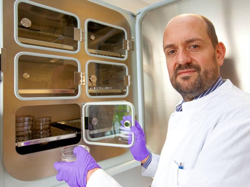 Mann in weißem Kittel vor geöffnetem Schrank mit Glastüren mit einer Petrischale in der Hand.
