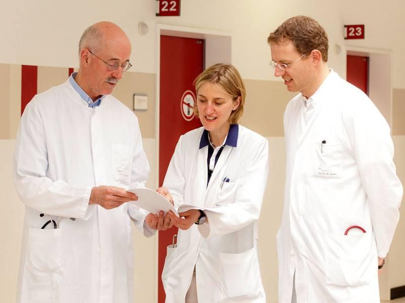 Eine Frau und zwei Männer in weißen Kitteln blicken auf ein Papier, dass die Frau hält.