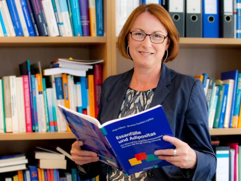 Frau ein geöffnetes Buch in der Hand haltend