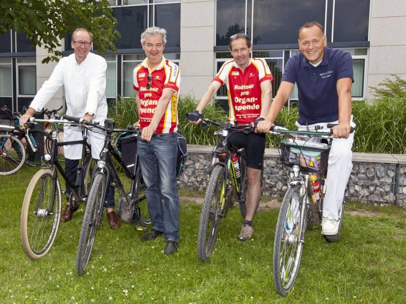 Vier Männer auf Fahrrädern.