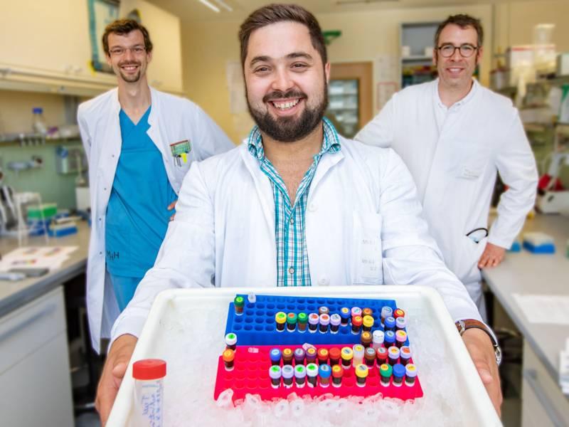 Drei Männer in weißen Kitteln in einem Labor, einer hält ein Gefäß in die Kamera.