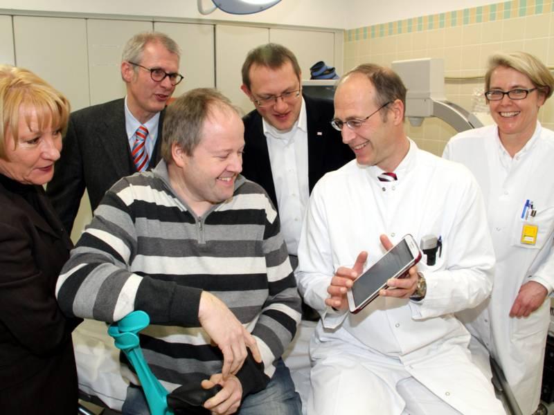 Ein Arzt im Kittel zeigt einem Mann mit Krücke ein Programm auf einem Tablet-Computer, drei weitere Personen sehen zu.