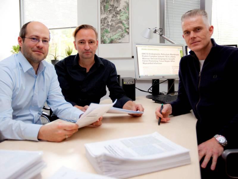 Drei Männer an einem Schreibtisch sitzend