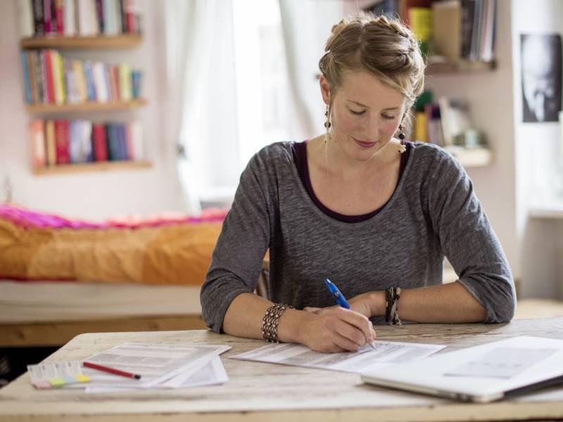 Frau an Tisch schreibend