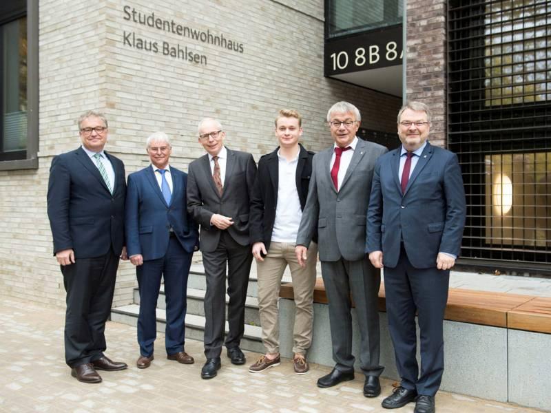 Sechs Männer stehen vor einem Gebäude.