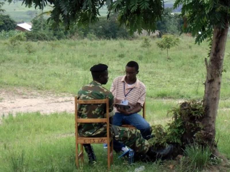 Zwei Männer sitzen auf Stühlen unter einem Baum.