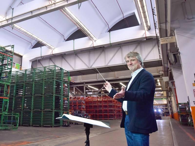 Mann mit Dirigentenstab in großer Fabrikhalle