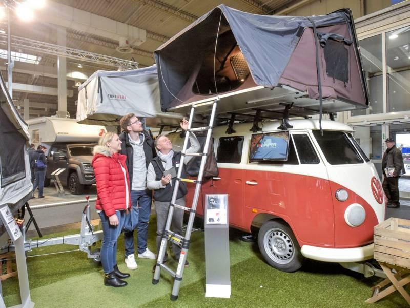 Eine Frau und zwei Männer vor einem VW Bulli Oldtimer mit Dachzelt in einer Messehalle