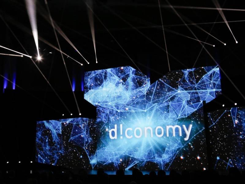 """Der Schriftzug """"d!conomy"""" angeleuchtet vor einem dunklen Hintergrund, im Vordergrund sieht man mehrere Köpfe."""