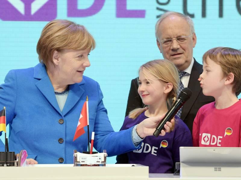 Eine Frau hält zwei Kindern ein Mikrophon hin, im Hintergrund ein Mann.