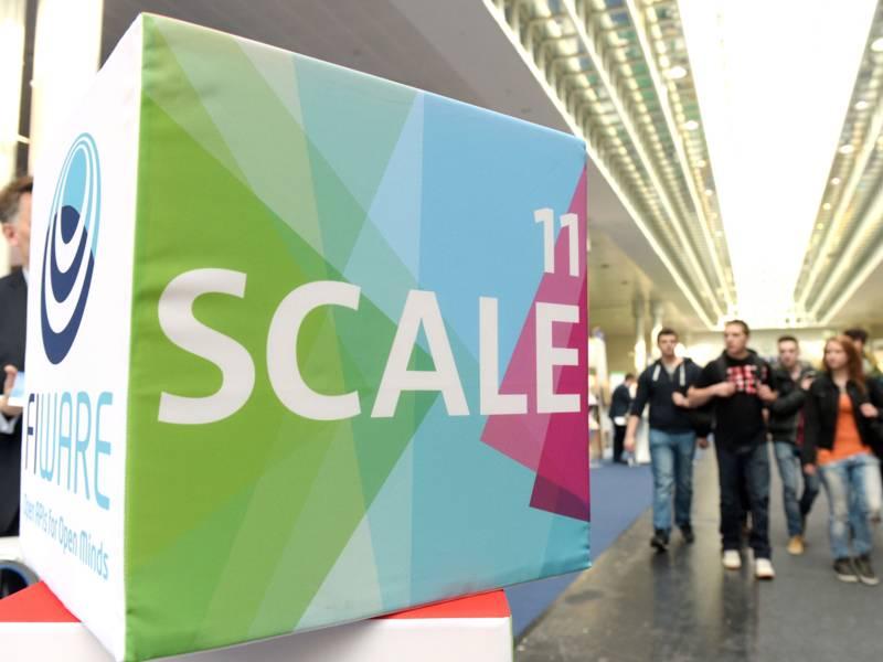 Der Schriftzug SCALE11 auf einem Klotz, im Hintergrund mehrere junge Menschen.