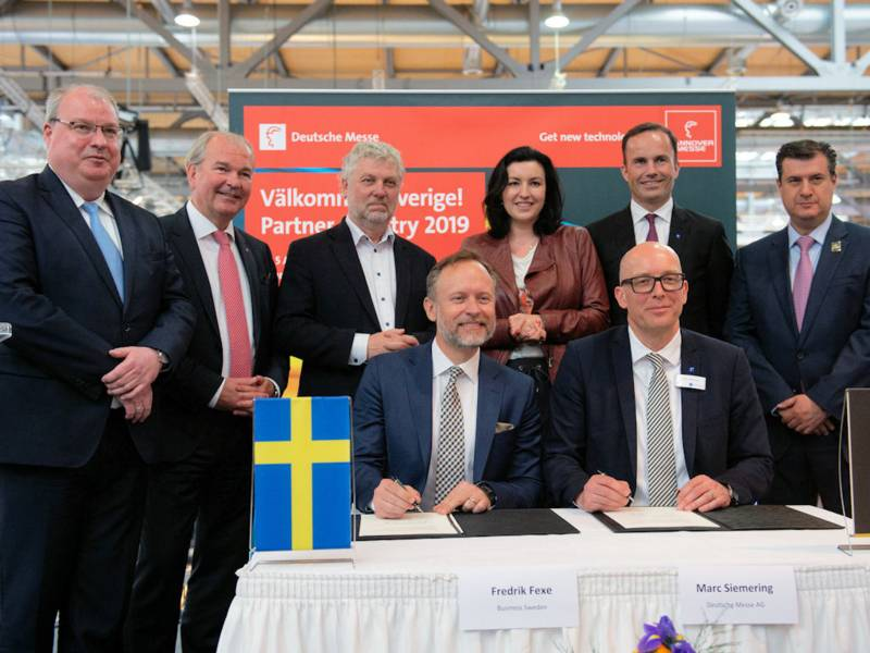 Menschen an einem Tisch mit schwedischer und deutscher Fahne stehend und sitzen