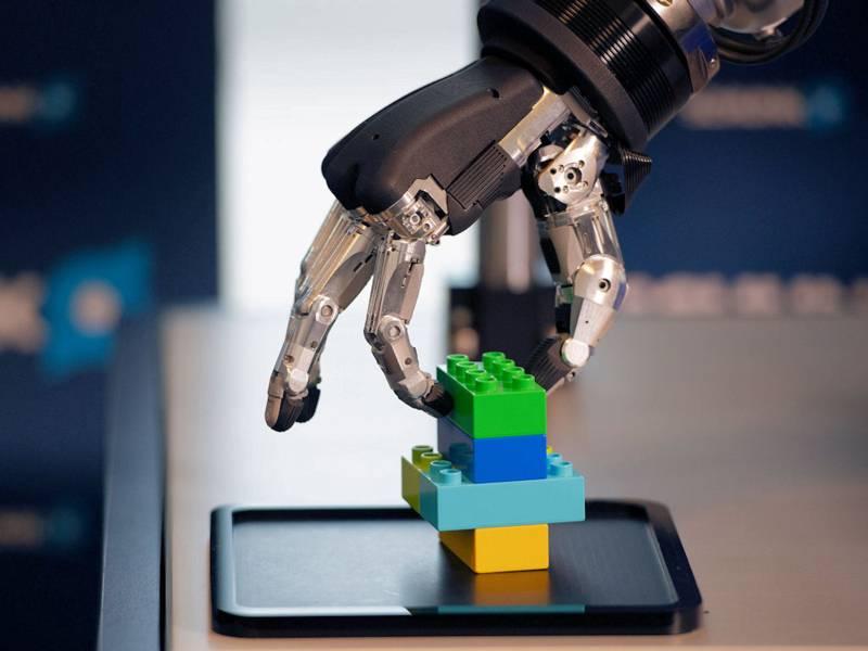 Roboterhand mit Legosteinen