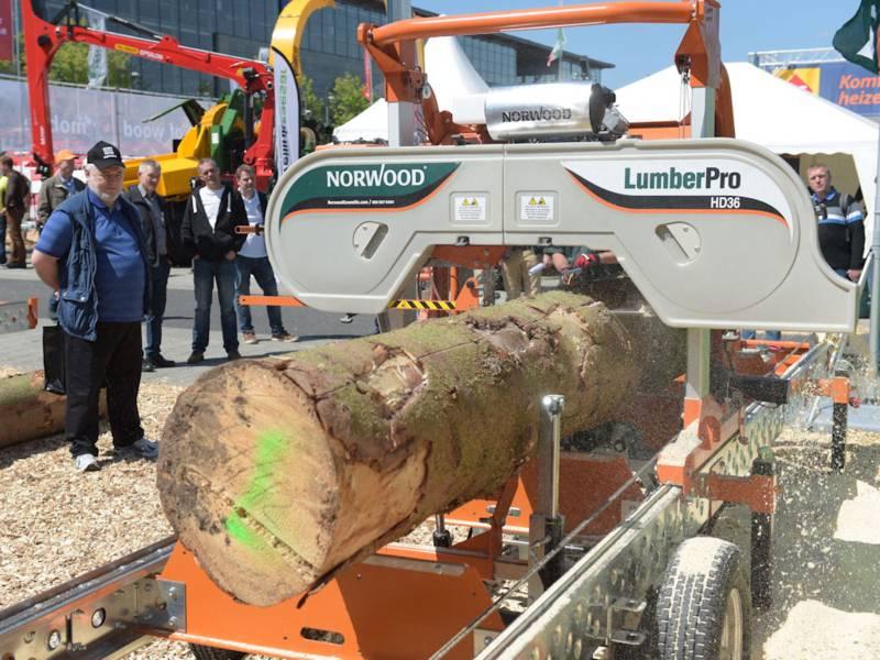 Holzstamm auf Fahrzeug wird maschinell zersägt.