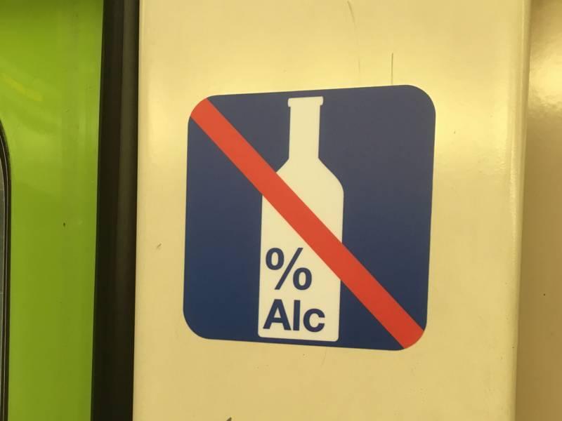 """Symbolbild mit einer durchgestrichenen Flasche, dem Prozentzeichen und der Aufschrift """"Alc""""."""
